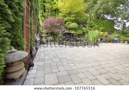 Backyard Garden Asian Inspired Paver Patio with Pagoda Pond Bronze and Stone Sculptures - stock photo