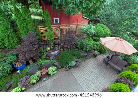 Backyard garden landscaping with paver bricks patio hardscape trees potted plants shrubs pond rocks furniture and red barn - stock photo