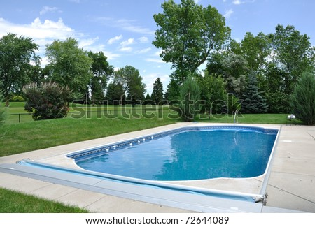 Backyard In-Ground Swimming Pool on a Sunny Summer Day - stock photo