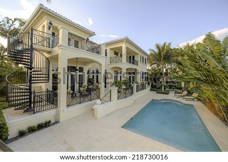 Backyard of luxurious mansion with in marble framed pool surrounded by Palm trees. - stock photo