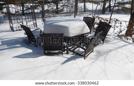 Backyard outdoor table and chairs on a patio covered with a thick layer of snow on a bright winter day - stock photo