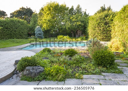 Backyard rock garden with outdoor inground residential private swimming pool and stone patio - stock photo