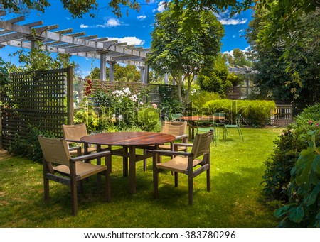 Backyard with garden table set in sunny a lush garden with shade of trees on a summer day - stock photo