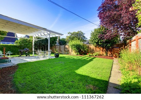 Backyard with  green grass  fence and house covered deck. - stock photo