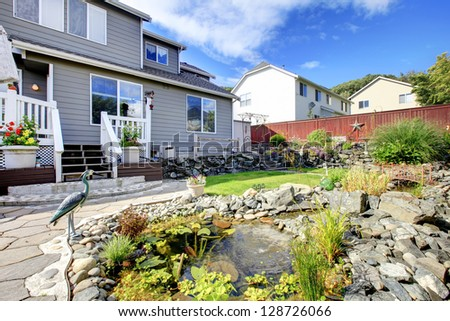 Backyard with porch, pond and rocks and red fence. - stock photo