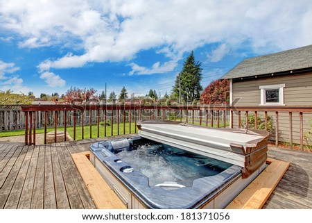 Backyard wooden deck with jacuzzi on it. Close up view of open jacuzzi and water in it. - stock photo