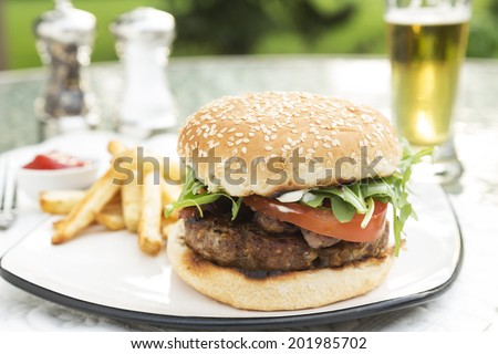 Bacon and Bleu Stuffed Cheeseburger topped with arugula tomato on a toatsed sesame seed bun served with fries ketchup and beer - stock photo