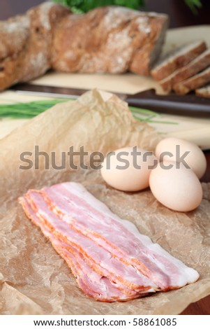 Bacon and eggs on waxed paper with chives and bread in the background. Ingredients for delicious breakfast. Shallow dof. - stock photo