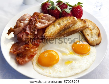 Bacon and eggs, with toasted croutons and strawberries.  A delicious breakfast. - stock photo