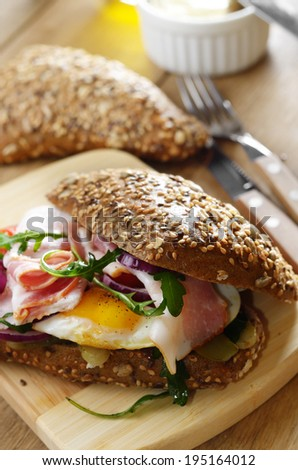 Bacon and fried eggs sandwich on the kitchen table - stock photo