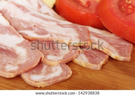 Bacon and Sliced Tomato on a wooden cutting board