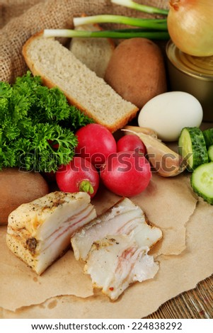 Bacon, fresh vegetables, boiled egg and bread on paper, on wooden background. Village breakfast concept.