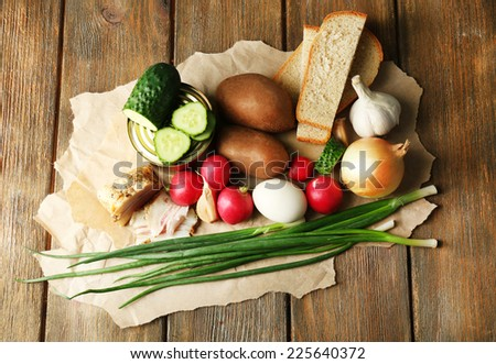 Bacon, fresh vegetables, boiled egg and bread on paper, on wooden background. Village breakfast concept. - stock photo