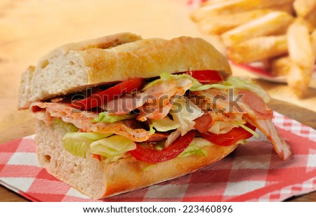 Bacon, lettuce and tomato (BLT) sandwich from freshly cut baguette on rustic wooden bread board with French fries in background.