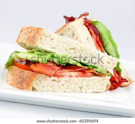 Bacon, lettuce and tomato sandwich on a white plate - stock photo