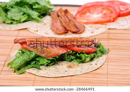 bacon lettuce and tomato sandwich on wrap with ingredients in the background - stock photo