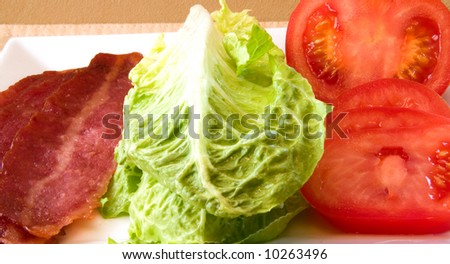 Bacon Lettuce Tomato on a white plate 3 Strips of bacon with crisp lettuce and sliced tomato. - stock photo