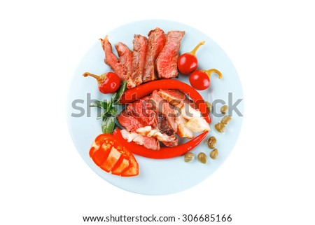 bacon meat slices served with tomatoes capers and red hot chili peppers on blue plate isolated on white background - stock photo