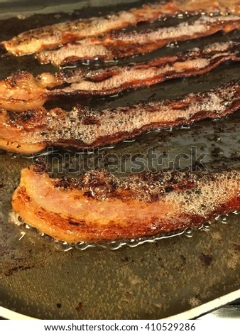 Bacon on a frying pan almost fully cooked.