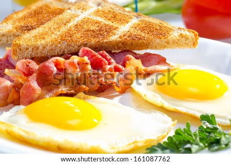 Bacon with sunny side up eggs served with toasts. - stock photo
