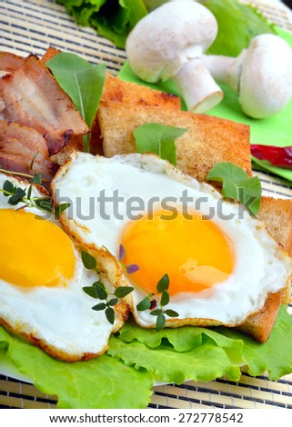 Bacon with sunny side up eggs served with toasts on a white plate - stock photo