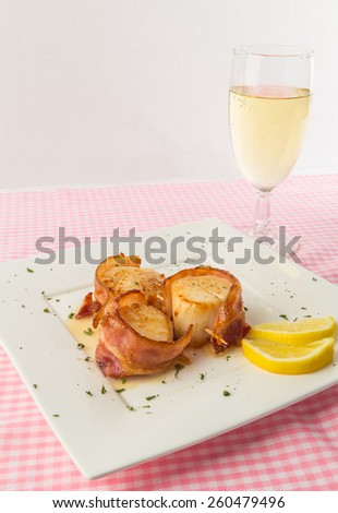 Bacon-wrapped sauteed scallops with stemmed glass of Mosel Riesling white wine on pink gingham tablecloth. - stock photo