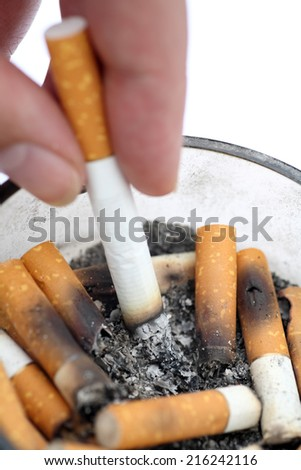 Bad addiction. Cigarette in woman's hand. Ashtray and cigarettes closeup. - stock photo