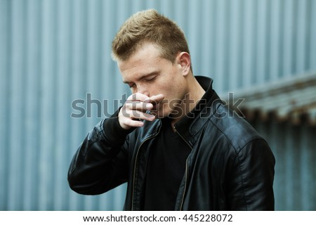 Bad boy concept. Portrait of brutal young man with short hair wearing black leather jacket, scratching nose over urban rusty corrugated background. Copy-space. Outdoor shot