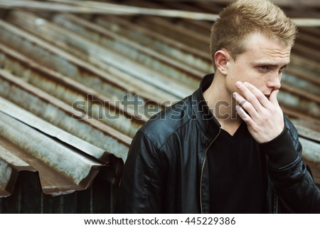 Bad boy concept. Portrait of brutal young man with short hair wearing black leather jacket, posing over urban rusty corrugated background. Copy-space. Outdoor shot