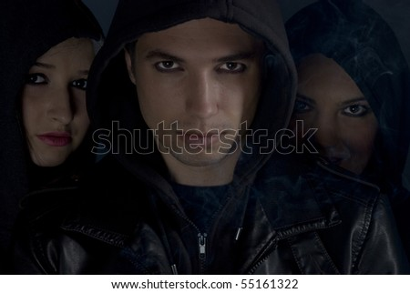 Bad boys concept,street people in darkness .Young man  the head of the  band  in front of two woman  with smoke around them - stock photo