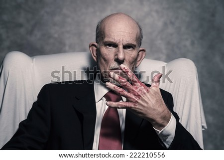 Bad businessman with bloody hands sitting in white chair. Gray beard wearing dark suit and red tie. Against grey wall. - stock photo