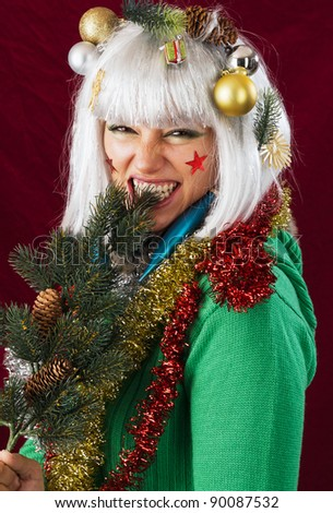 Bad Christmas woman. Funny studio shot against a dark red background. - stock photo