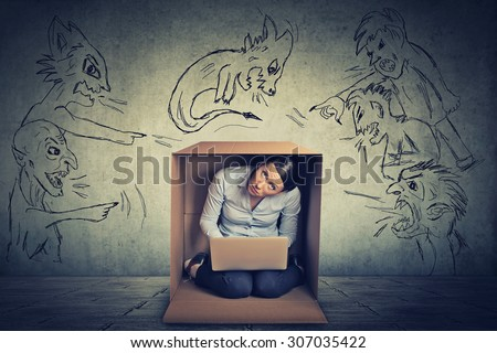 Bad evil men pointing at stressed woman. Desperate scared businesswoman hiding in a box working on laptop grey office wall background. Negative human emotions face expression feelings life perception - stock photo