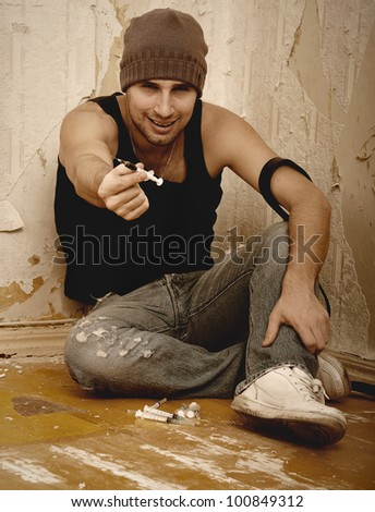 bad man - drug dealer with syringes and  with drugs sitting on the floor - stock photo