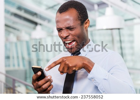 Bad news. Frustrated young African man in shirt and tie talking on the mobile phone and touching head with hand while standing indoors - stock photo