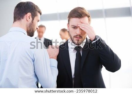 Bad news. Rear view of young businessman consoling his depressed colleague and holding hand on his shoulder with people standing in the background  - stock photo