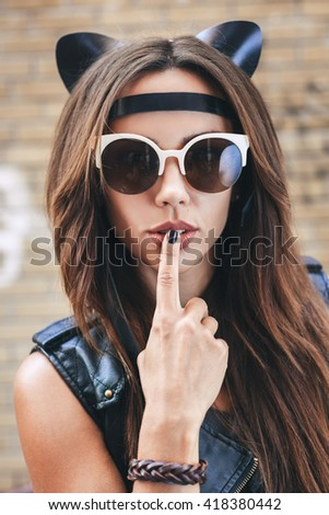 Bad sexy woman in sunglasses with leather cat ears. Urban scene. Outdoor lifestyle portrait - stock photo
