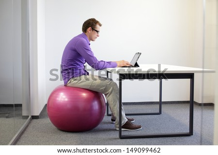 bad sitting posture at tablet  - business man on stability ball in his office - stock photo