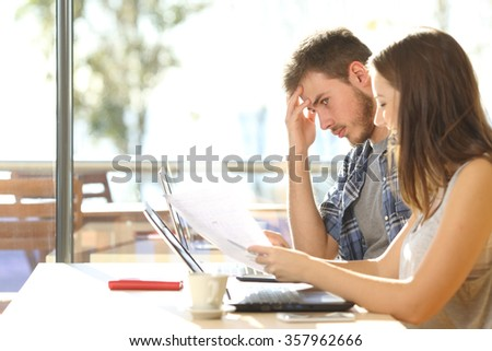 Bad student learning with difficulties and a friend teaching him in a campus bar - stock photo