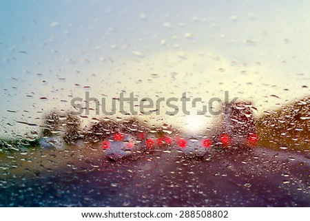 Bad Weather Driving - traffic jam on a highway - selective focus on raindrops on the windshield  - stock photo