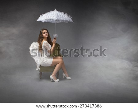 bad weather from sky concept, angel with umbrella - stock photo