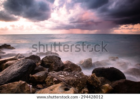 Bad weather. Stormy weather on the stone coastline during a sunset. Rain on the horizon. Long exposure - stock photo