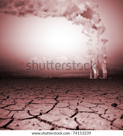 Badly cracked earth with power station - stock photo