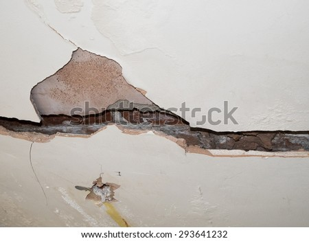 badly cracked plasterboard on interior wall showing bricks behind