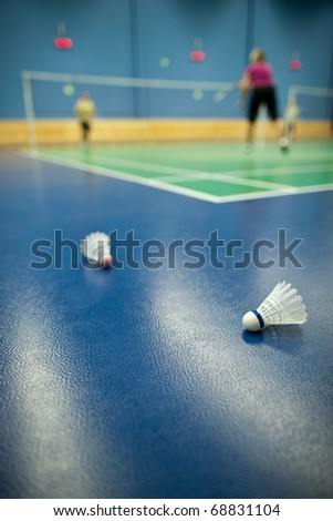 badminton - badminton courts with players competing; shuttlecocks in the foreground (shallow DOF; color toned image) - stock photo