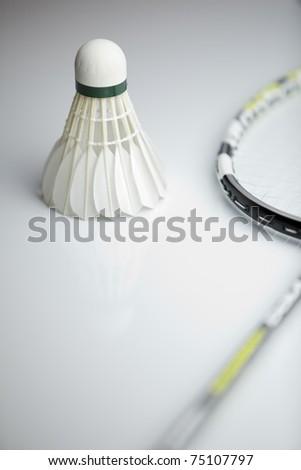Badminton shuttlecock and racket on white background (shallow DOF; color toned image) - stock photo