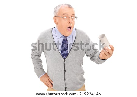 Baffled senior holding an empty toilet paper roll isolated on white background - stock photo