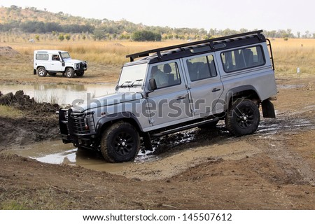BAFOKENG - MAY 18: Silver Land Rover Defender 110 SW going through water obstacle at new 4x4 track opening event May 18, 2013 in Bafokeng, Rustenburg, South Africa   - stock photo