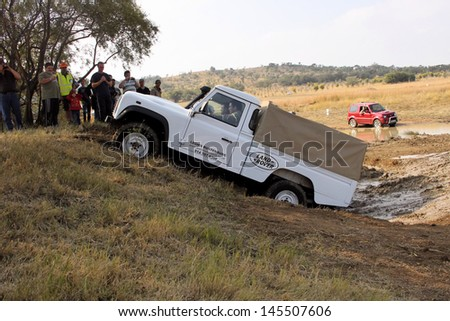 BAFOKENG - MAY 18: White Land Rover Defender 110 HC scaling steep obstacle at new 4x4 track opening event May 18, 2013 in Bafokeng, Rustenburg, South Africa   - stock photo