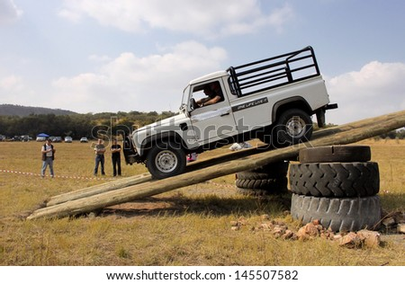 BAFOKENG - MAY 18: White Land Rover Defender 110 HC scaling tilt bridge obstacle at new 4x4 track opening event May 18, 2013 in Bafokeng, Rustenburg, South Africa   - stock photo